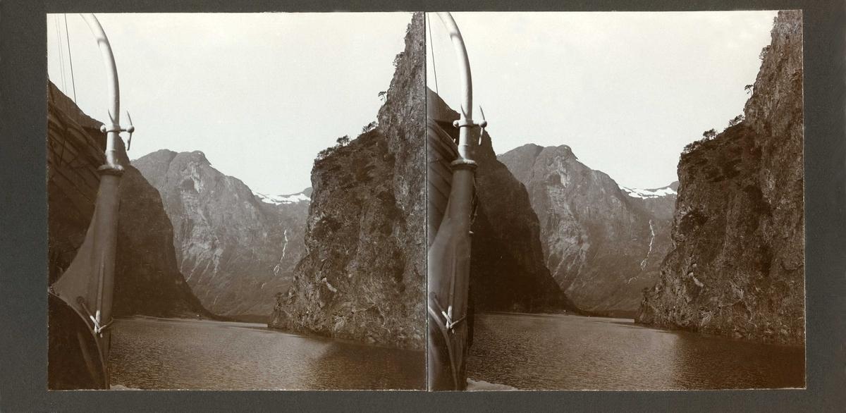 """Stereoskopi. Fjellandskap fotografert fra båt (D/s """"Hornelen""""); Nærøyfjorden."""