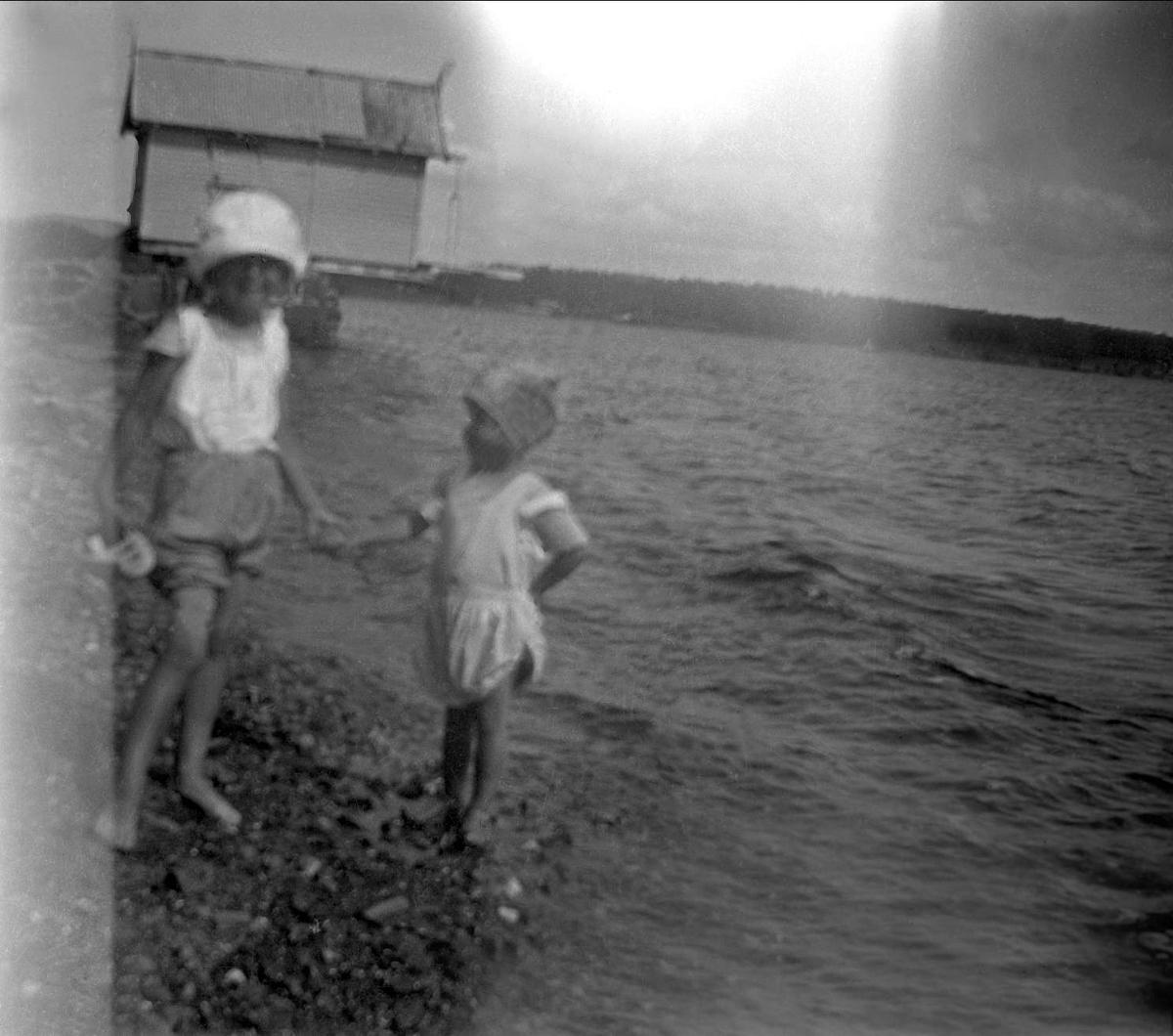 To barn holder hender ved sjøen. Et naust i bakgrunnen. Robsahm og Lund.