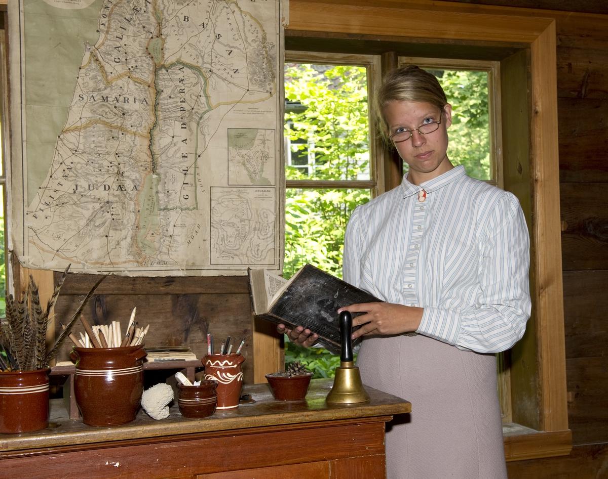 På historisk ferieskole får barn kjennskap til tradisjoner og historie gjennom opplevelser, lek og læring. Her står frøken Åse i skolestua med en bok, antakelig bibelen.