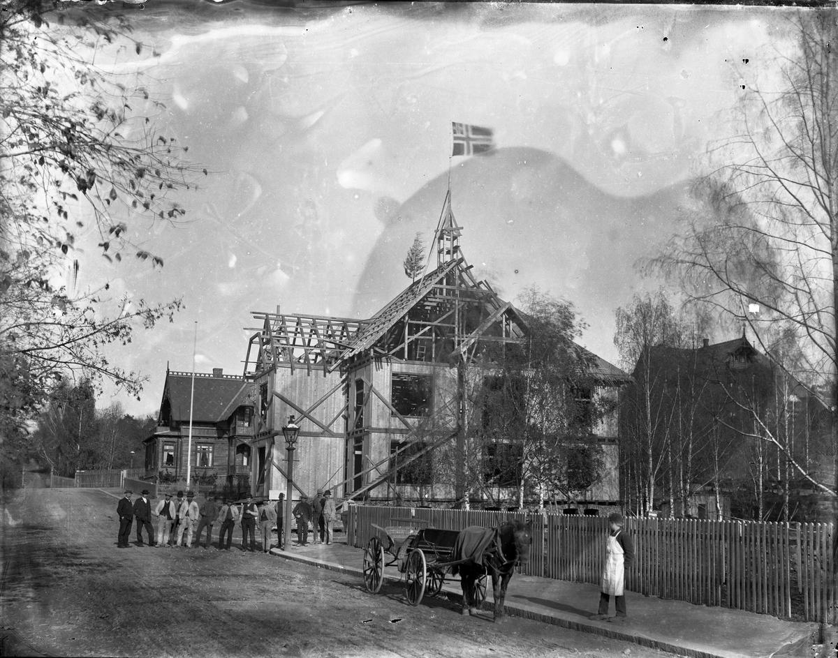 Hus under bygging, unionsflagg og mønsåstre på taket, ukjent sted. Gruppe arbeidere på veien foran huset. Langs et stakittgjerde står en visergutt med forkle og en hesteskyss.