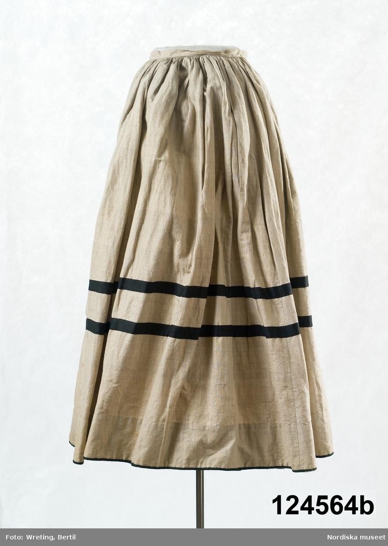 2-delad klänning i  modesnitt från 1870-talet. Med liv och kjol av oblekt fintrådig bomullslärft. varpen vanlig bomullstråd medan inslage tär en glansigare tråd. Handvävt med små vävfel.  a. Livet, höftlångt, figursytt. 2 framstycken, släta och något utställda nedtill i sidsömmarna. Nederkanten något svängd. 4 ryggstycken insvängda i midjan för att sedan vidgas i ett rundat skört. Nederkanten kantad med 2 cm brett svart bomullssatinband. Isydd ärm med 2 sömmar. Tät halsringning med låg ståndkrage. Knäpps med 7 blanka vitmetallknappar och tränsade knapphål.  Sydd på foderstomme av  smalrandig bomullslärft i beige med gul/brun rand. Handsydd med  hårdtvinnad bomullstråd.  Anm. 1 knapp saknas. Något solkig. b. Kjol, hellång, 1 framvåd. 3 bakvåder och 2 sidvåder, alla sneddade. Framvåden slät, de övriga rynkade  mot 2 cm bred midjelinning. sprund i vänster framsöm, knäppning med  hake och hyska. kjolen kantad med ett smalt svart band och med 2  bredare dekorband runt  kjolen 30 cm från kanten. Kjolskoning 10 cm bred av ljusbrun bomullslärft. Kjolen handsydd. /Berit Eldvik 2011-01-12