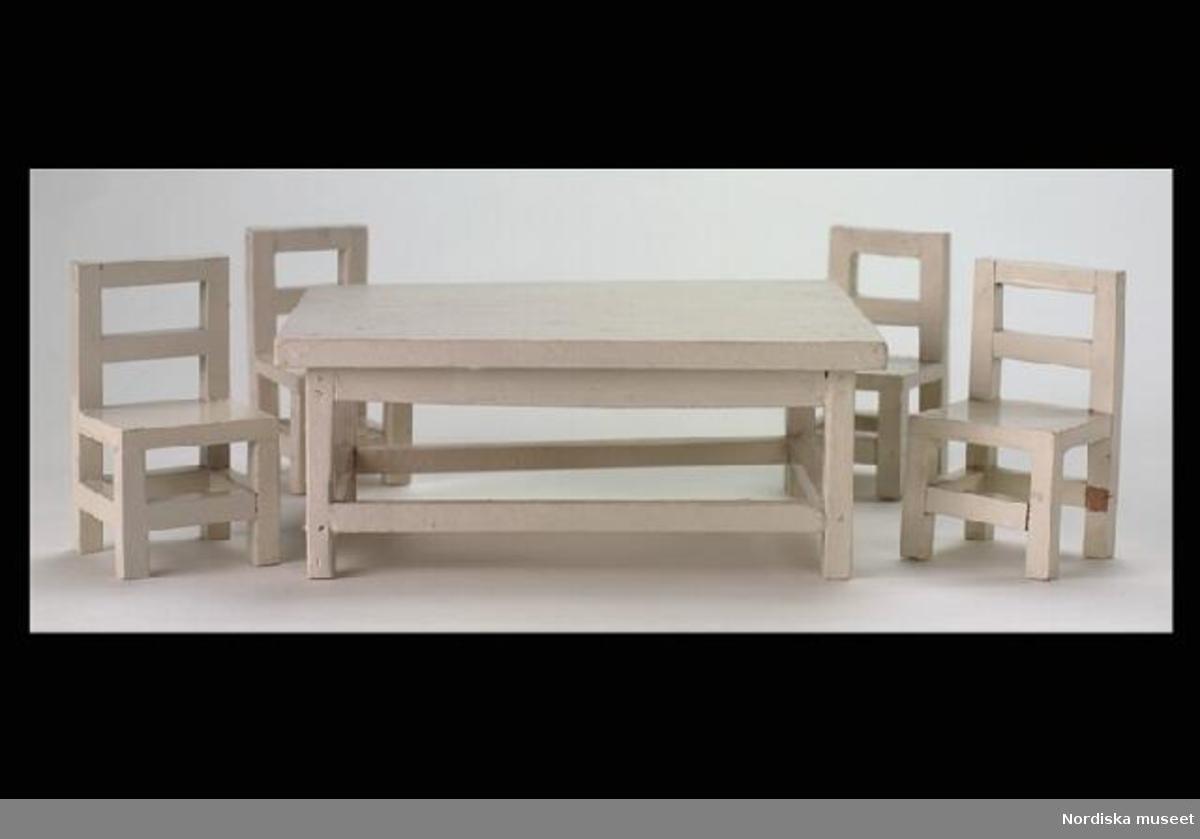 """Huvudliggaren: a-b """"Stolar, ett par, leksaker, trä, rak typ, ryggstöd med horisontal slå, benen förbundna med slåar, fyrkantiga; itappade; vitlackerade; köksstolar i dockskåpet [220.405].""""  Inventering Sesam 1996-1999: B 5,5 cm Djup 5,2 cm H 9,8 cm Ett par stolar av vitmålat trä, ett överstycke och en ryggslå, ramslåar mellan benen runt om, kantig modell utan utsmyckningar. Har lekts med av fröknarna Catarina f. 1919 och Anne-Sophie f. 1921 von Heidenstam, döttrar till givaren. Tillhör dockskåp inv.nr 220.405 med inventarier 220.406--220.760. Helena Carlsson 1997"""