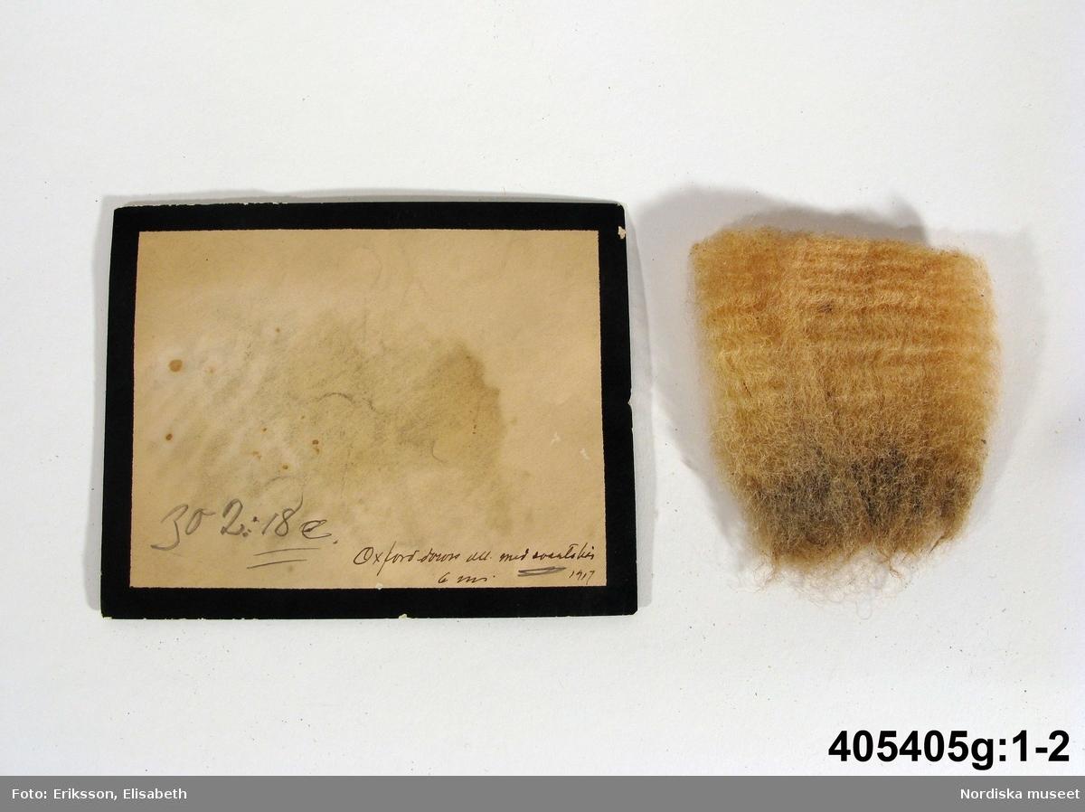 """Ullprover 8 st, inlagda i 8 kuvert med svart kant, sorgkuvert,  Handskriven text på kuverten: a:1-2) """"302:2a Cheviot ull ca 6 m 1917 [m=månader, ålder på fåret ullen kommer ifrån] b:1-2) 302:2b Normal cheviot ull ca 6 m 1917 c:1-2) 302:18a Oxforddown ull (Tacka) 6m 1917 d:1-2) 302:18b Oxforddown efter bl. tacka, 6 m 1917 e:1-2) 302:18c Oxfordd. ull efter importerad Bagge 6m 1917 f:1-2) 30218d Oxfordd. fader & blandat Moder... 6m 1917 g:1-2) 302:18e Oxford down ull med svarta hår 6m 1917"""" h:1-2) 302:20 Shropshire ull (fin) ca 6 m 1917 /Elisabet Hidemark/ Dessa prover ingick ursprungligen i en större samling ullprover insamlade av lantbruksinspektör Aug. Lyttkens, Stockholm, som skänkte samlingen till Lantbruksakademiens Lantbruksmuseum 1921-1922. Se Lantbruksmuseet katalog sid 594. nummer 302. (a:1, b:1 osv = ullproverna. a:2. b:2 osv = kuverten) /Berit Eldvik 2008-03-25"""