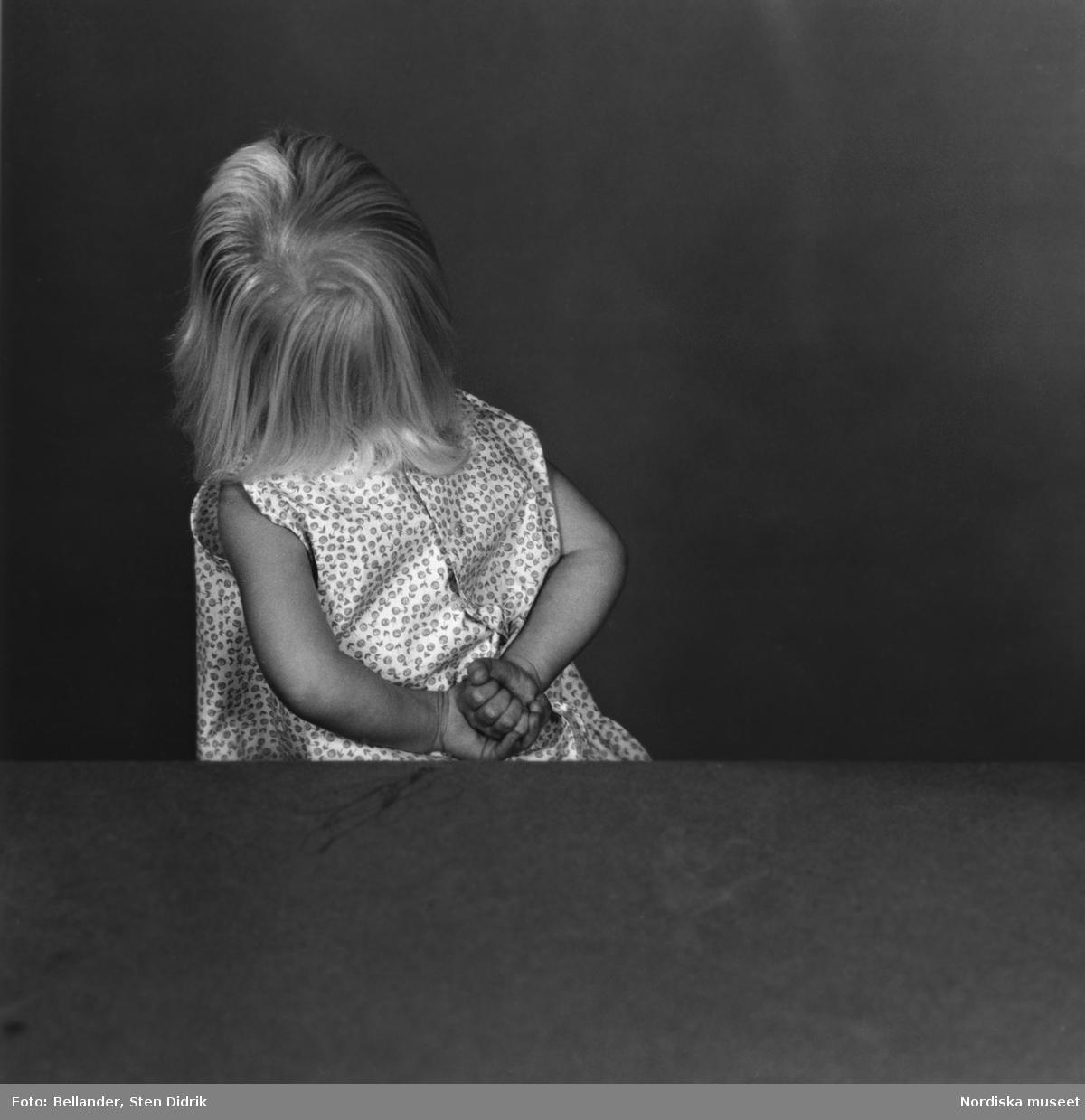 Barnporträtt. Liten flicka i blommig sommarklänning har vänt sig bort från kameran med händerna på ryggen.