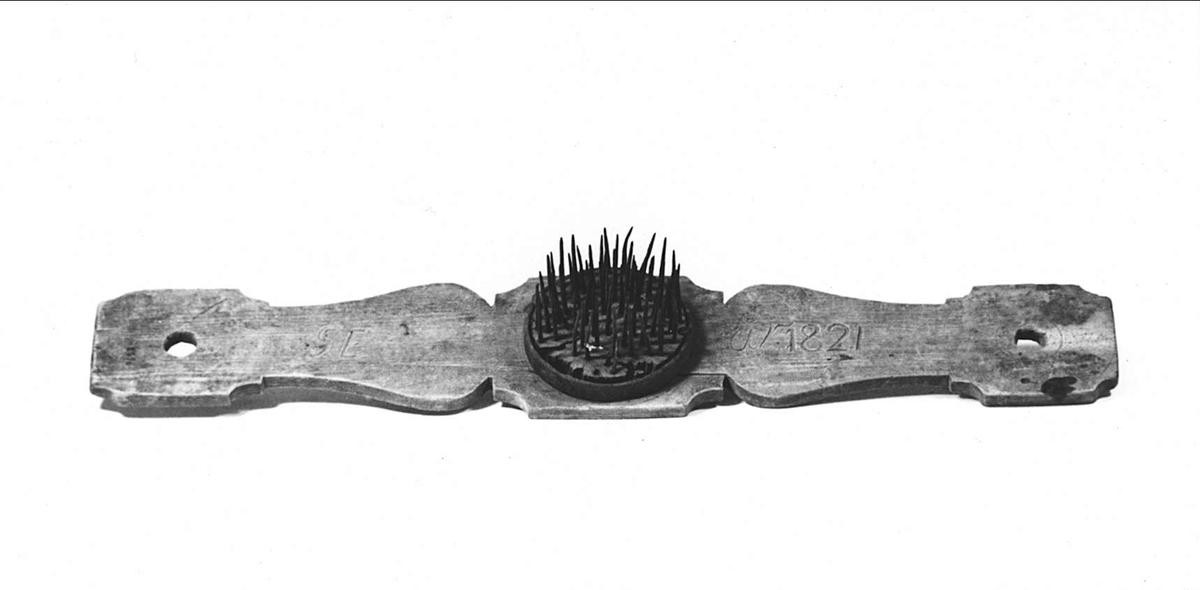 Häckla av trä, med piggar av järn. Inskuret: GE år 1821.