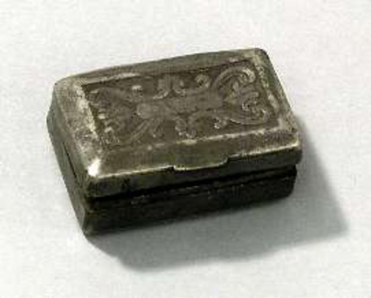 Dosa, mycket liten, av tenn. Reliefdekor på lock och undersida.