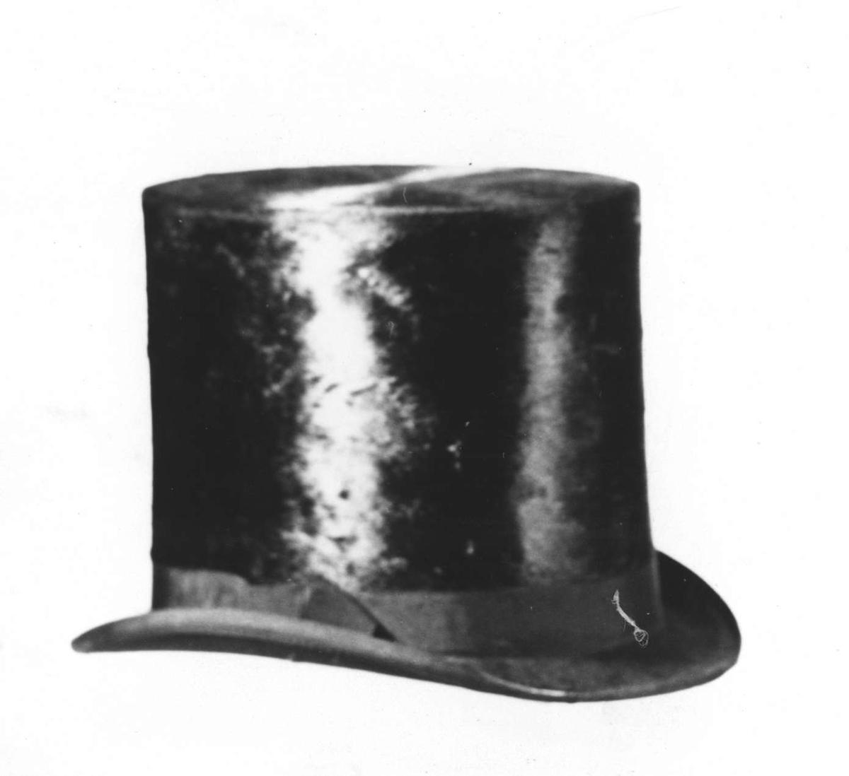 Hög hatt av svart felb. Runt kulle och brätte svart ripsband. Brättets undersida klätt med svart ylletyg. Pappfoder.