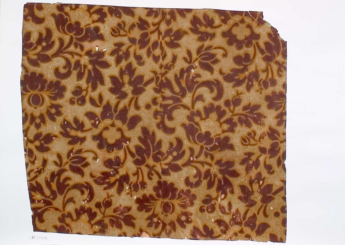 Tapetprov med tryckt mönster i brunt och brungult. Handskriven text på baksidan av kartongen: Nr 66 Kv. Svalan nr. 7 gatuhus n.b. rum 6 (mellanlager) 2.