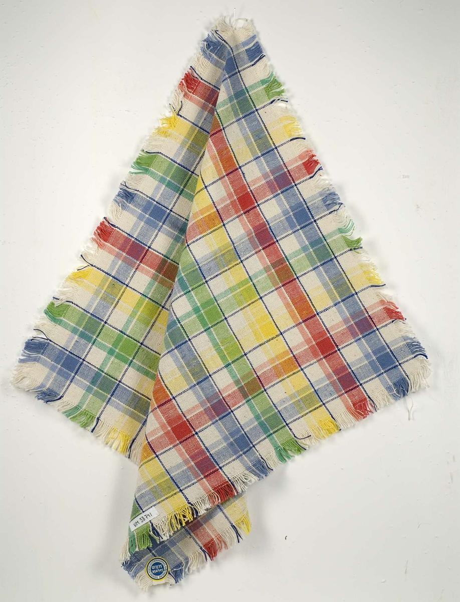 Rutmönstrad duk med kort frans. Duken är vävd i tuskaft av vitt, gult, blått, och rött cottolingarn. Duken är märkt B2884.