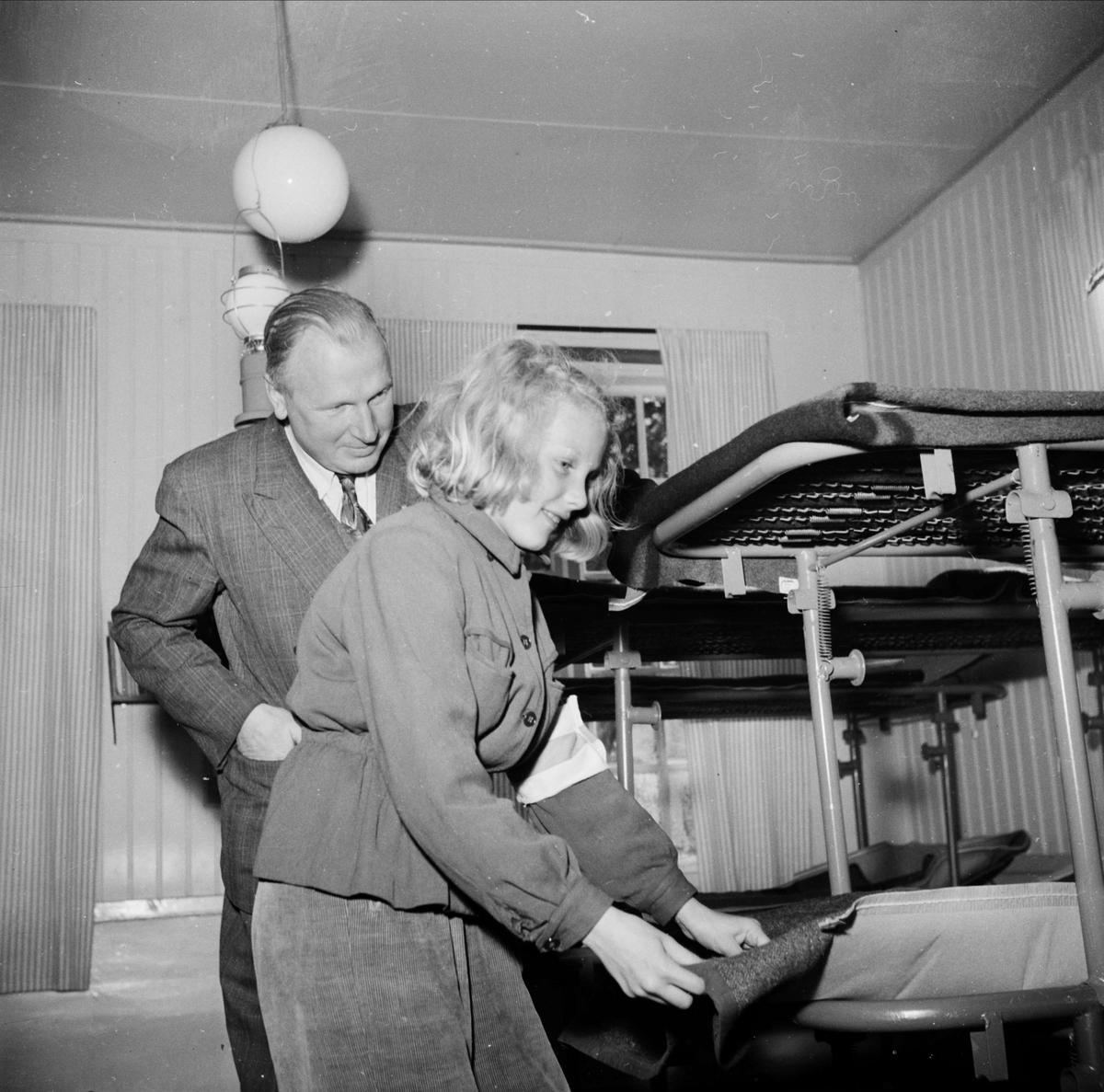 Byrådirektör Herman Löfgren i civilförsvarsstyrelsen ser på när Birgitta Tegelberg bäddar sin säng i skolinternatet, Kyrkskolan i Vendel
