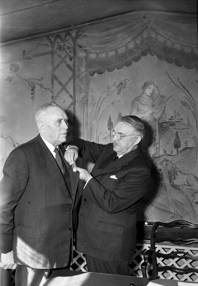 Landshövding Hilding Kjellman fäster medalj på äldre mans kavaj, Uppsala, sannolikt 1952