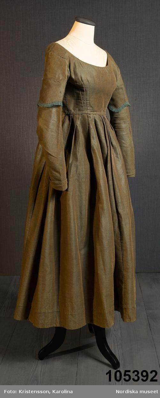 Hel klänning i 1830-talets modesnitt, av fint halvylletyg i kypert med varp av ljusbrunt bomullsgarn och inslag av grönt tunt glansigt redgarn som ger en grönskimrande yta. Livet går ned nästan till midjehöjd, figursytt med 2 framstycken med bakåtflyttade sidsömmar, ett ryggstycke med 6 inprovningar fördelade i två grupper. Vid båtringad halsringning, knäppning med tätt sittande hakar och hyskor. Isydda långa ärmar svängda med 2 sömmar  med 3 veck vid armbågen. Ärmsprund knäppt med hyska och hake samt 4 cm uppslag med rundade hörn. Upptill på ärmen besättning av tyget med stora rundade uddar kantade med klargrön bomullsfrans.  Passepoaler av tyget i alla sömmar. Livet fodrat med skotskrutig bomullslärft i rött, grönt, gult och vitt och i ärmarna ett smalrandigt bomullstyg i blått och rosa. Kjolen sydd av  5 våder, lagda veck runtom i midjan. sprund mitt fram. Uppsytt veck  en decimeter från fållen. Skoning med brun bomullslärft. Handsydd. Har burits 1838 som ungmorsklänning, alltså av bruden dagen efter bröllopet, av Maria Margareta Mårtensdotter från Kysings, Vall sn på Gotland. Möjligen tillsammans med sidenhalsklädet 105385. Anm. I  gott skick. OBS Klänningen sitter bakochfram på fotona, knäppningen är fram. /Berit Eldvik 2011-06-13