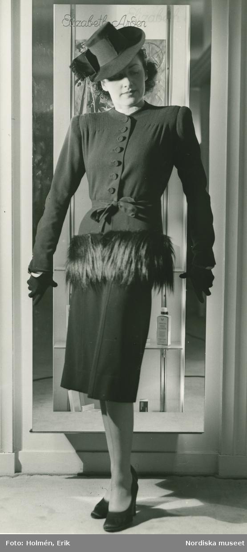 Helporträtt av kvinna i dräkt med pälsdetalj och hatt.