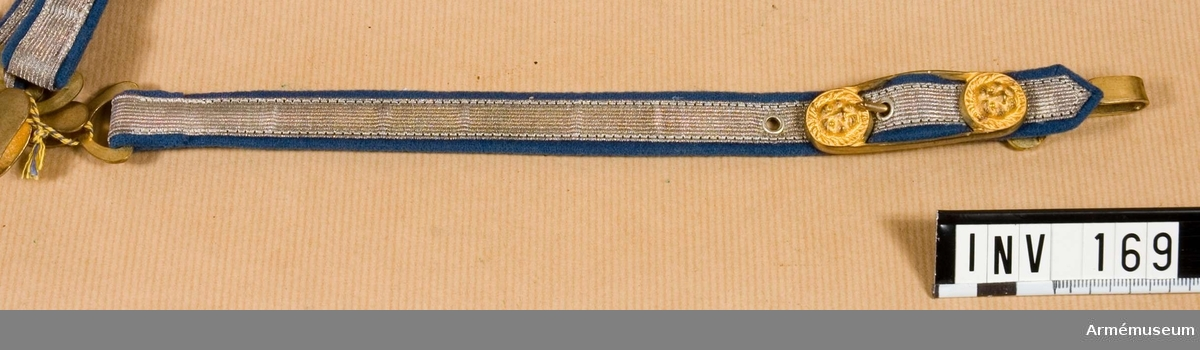 Dragrem av silvergalon, denna är 13 mm bred. Foder av blått  kläde. Långsmalt spänne av gulmetall, 60 mm långt och 20 mm  brett, m två lejonhuvuden, ett i var ände. En hake i var ände. Källa: Knötel, band II Formations und Uniformierungsgesichte.