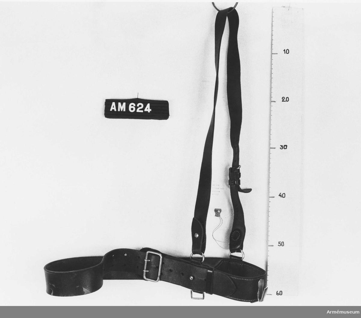 Samhörande nr är 624-625. Livrem med axelrem m/1937. Livrem och axelrem i brunt läder med spänne och övriga metalldelar av vitmetall, m/1937 för officer och underofficer. Livremmen sammanhålles genom ett kraftigt spänne (40x60 mm) med två torn. Livremmens tamp fasthålles i sitt läge med en sölja och en kraftig knapp på hals. En kraftig krok och tre olikformade ringar håller bajonetten på plats. Axelremmen fästs vid livremmen medelst två ringar. Remmen är ställbar med spänne med torn, hål och sölja.