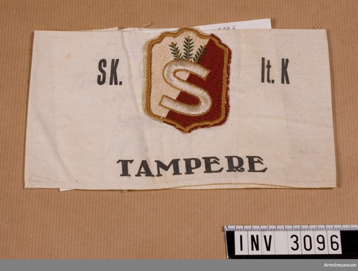 """Av tuskaftsväv med svart tryck """"SK""""=skyddskår, """"It.K""""=  luftvärnskompaniet och """"TAMPERE""""=Tammerfors. En maskinbroderad sköld är fastsydd på yttersidans övre del. Skölden är delad i ett vitt och ett rött fält, något diagonal delning. Ett """"S"""" krönt med tre kvistar. Använt av Esko Renholm.  Samhörande nr är 3096-3097."""