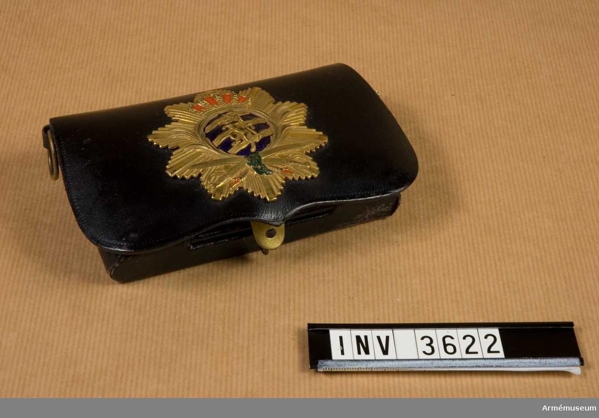 Väska av svart lackerat läder med vapenplåt med Göta rikes vapen ett upprest krönt lejon Över tre strömmar i guld Över mörkblå emalj. I väskan plats för 10 patroner. I ringarna på  sidorna skall remmen fästas.