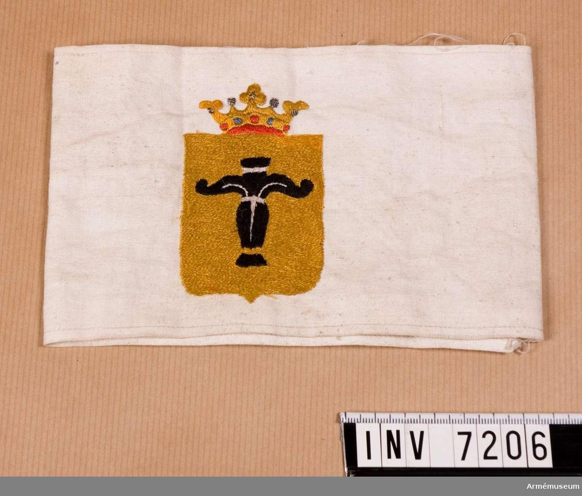 """Sydd av vit linnelärft och med broderad gul sköld med Vasa vapen. Har varit utställd i Bernadottevåningen och borttagen 1982. Svenska brigarden. I finska inbördeskriget 1918 en av svenska frivilliga militärer och civila bildad trupp på 300-400 man som med utmärkelse deltog på """"de hvites"""" sida bl a i erövringen av Tammerfors (mars-april).  Samhörande nr är 7202 - 7210."""