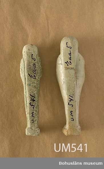 Ur Ur Knut Adrian Anderssons katalog II Uddevalla - Musei - Historiska - Samlingar: E: Utländska föremål De Etnografiska föremålen upprättad år 1916: No 58. Två Mumiebilder (10,5 x 3 x 1,5 och  9,6 x 2,5 x 1,5 centimeter) med hieroglyfer. Sk. 1883 av Carl Christiansson. Från Egypten.  Ur handskrivna katalogen 1957-1958: Två mumiebilder m. hieroglyf Egypt. L. 10,8 Br. 3,2 resp. L 9,9 Br. 2,4. Ljust gröna (lergods?) Den ena glaserad. Föremålen hela.  Lappkatalog: 100