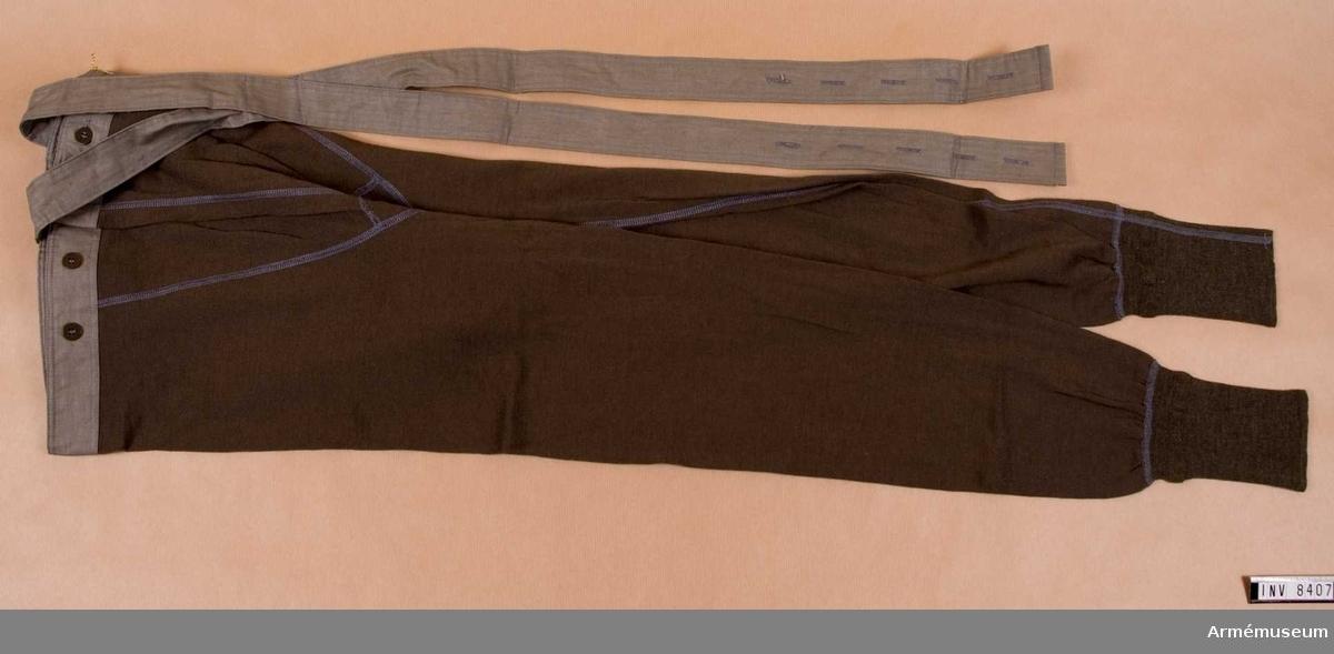 Samhörande nr är 8406-7.   Kalsonger av ylle med hängslen. Linningen är klädd med grått bomullstyg. I livet bak sitter två hängslen, korslagda i  nacken, även dessa i bomullstyg, grått.