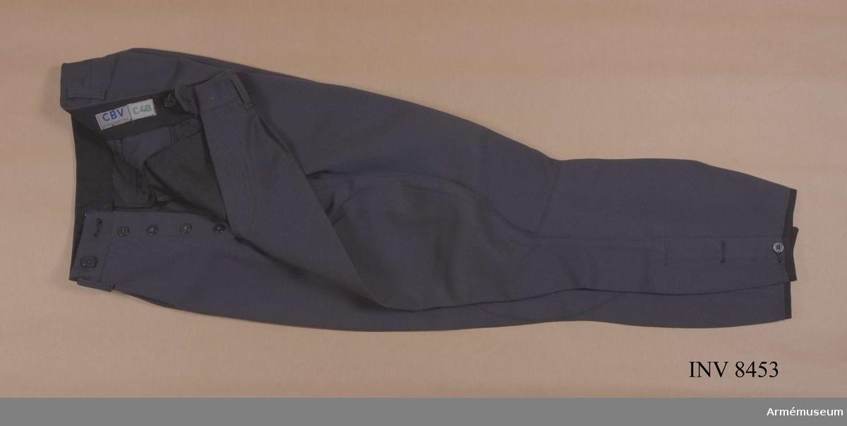 Tillverkade av stålgrått ylletyg, diagonalvävt, har två  sidfickor, två bakfickor, ballongskärning och hällor för bälte. Byxorna har stålgrå skoning av tyg - kan vara av skinn. Byxorna är tillverkade vid CBV Centrala beklädnadsverket. Är i storlek C 48.