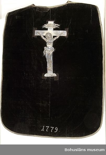 """Föremålet visas i basutställningen Uddevalla genom tiderna, Bohusläns museum, Uddevalla.  Mässhake från Uddevalla kyrka i svart bomullssammet kantad med band av silvertråd; krucifix i silverplåt eller försilvrad plåt på ryggsidan. Fodrad med ett mörkt brunt glättat linnetyg. Pålött på krucifixet: """"INRI"""" och """".C.W.:.M.S. Dn 2 Aprilii 1732"""". Vid nederkanten på baksidan finns årtalet """"1779"""" i form av påsydda metallsiffror. Enligt Sten Kristiansson, Uddevalla stads historia II, Uddevalla 1953, s. 363, syftar initialerna på handelsmannen Carsten Werner, som den 2 april 1732 gravsattes i Uddevalla kyrka, och hans hustru Maren Sahlgren.  Enligt Marie-Louise Franzén, Statens Historiska museum, Stockholm i december 2002: Mässhakar av denna typ är ovanliga i Sverige. Det finns mycket få bevarade. I Historiska museets samlingar finns inte någon enda mässhake från Bohuslän.  Ur handskrivna katalogen 1957-1958: Mässhake, U-a kyrka H. 106 resp. 123 cm. svart sammet, silverstickn. krusifix i försilvr. plåt; mont. som föreg. (UM1933)  ramen 140 x 107 cm.""""1779"""" 1732  Lappkatalog: 12"""