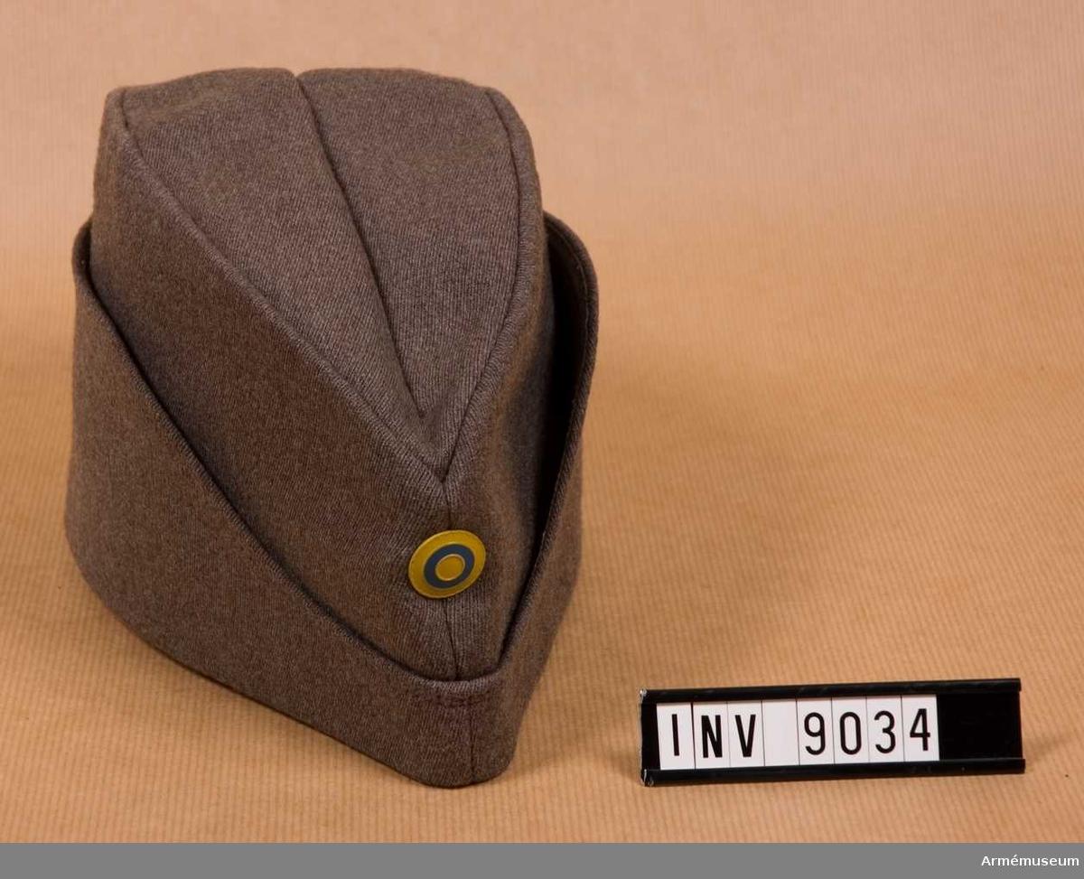 """Sydd i gråbrungrön yllediagonal med svettrem, foder och uppslag. Uppslagen kan vikas ned till skydd för öron och nacke. Mitt fram nationalitetsmärket m/1941. Mössan är i fodret märkt med tre kronors-stämpeln, 59, Ö.S.B. Siffrorna """"59"""" betyder storleken på mössan."""