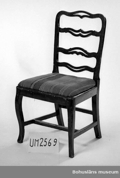 """Ur handskrivna katalogen 1957-1958: Stol, brunmålad H. 92 Sitsens L. 49 Br. 41,5. Sitsen överdragen m. rutigt tyg. Färgen något flagnad. Hel. Ugglehult, Bäve, Bohuslän.  Lappkatalog: 82 September 2008: Enligt Birgitta Martinius, Mölndals stadsmuseum, som undersökte vad våra samlingar innehåller av lindometillverkade möbler, är detta en stol från 1700-talets slut tillverkad i Lindome.  Litteratur: Antik & Auktion 10/2012. Artikel """"Arvet från Lindome"""", Christina Linderoth-Olson. Martinius, Birgitta. Stolar från Lindome 1740 - 1850. Ica Bokförlag 2012."""