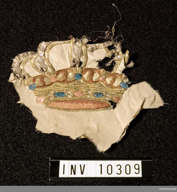 Grupp B I.  Duk av fyrskaftat vitt fansiden med broderade emblem: i mitten Karl XIV Johans namnchiffer i guld under sluten krona, rött foder, blå och röda stenar, silverpärlor. I hörnen samma namnchiffer på blå botten under liknande krona.