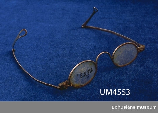 Ur handskrivna katalogen 1957-1958: Två par glasögon a) Bågarnas L. 10,5. Skalmarnas L. 11,5 resp 10. Föremålet helt. - b) Bågarnas l: 12. Skalmarnas l. vardera 14,5. Lagade.  Lappkatalog: 93