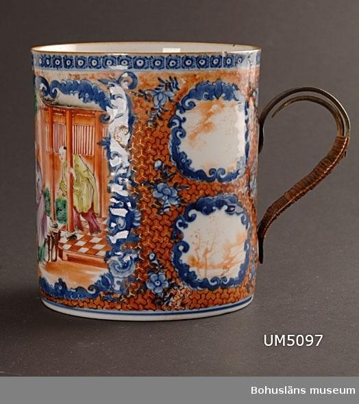 Föremålet är tillverkat i Kina, troligen gjort för den europeiska marknaden. Cylindriskt kärl med hänkel. Hänkeln är av metall och omlindad med flätad rottingliknande träfiber. Dekor i underglasyrblått samt polykrom målning över glasyren. Dekoren består av mönsterbårder och blommor samt ett motiv med figurer med en byggnad i bakgrunden.  Ur handskrivna katalogen 1957-1958: Kinesisk mugg, röd-blå Mynningsdiam. 11,7-12,5 H: 13,8. Av porslin. handtag av bastomvirad metall. Mycket obetydligt skadad  Lappkatalog: 62