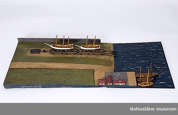 """Modell av varvet Lyckans Slip i Fiskebäckskil på Skaftö. Modellen är monterad på en rektangulär träplatta och  består av två skepp upplagda på land, tre båtar i sjön och några hus. Framtill på långsidan står det: LYCKANS-SLIP. På kortsidan står det LYCKANS-SLIP J.E.OLSSON 1944. Undertill står det: """"Den mörka träbiten har tillhört Johannes Janssons vindstrappa i Fiskebäckskil (ålder över 200 år).  För ytterligare information om John Emil Olsson och förvärvet, se UM005807.  Ur handskrivna katalogen 1957-1958: Lyckans slip Modeller på platta. Plattans mått: 65,5 x 27. Föremålen hela. Från kapten Olssons saml., Fiskebäckskil.  För ytterligare information om förvärvet, se UM005087.  Föremålet presenterat på Bohusläns museums hemsida år 2009 - 2013, webbutställning """"John Emil Olsson Fiskebäckskils sjöfartsmuseum""""."""