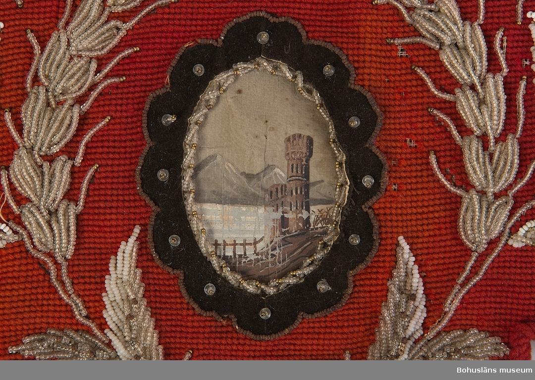 """Bred hyllbård med spetsig udd. Broderad i petit points med rött ullgarn (över extra ylletråd?) på stramalj. I mitten en oval medaljong med motiv av borg, sjö och berg, målat på siden. Runt denna en ram av  brun sammet klistrad på papper, samt pärlbroderi. Vid sidan av mittmedaljongen broderade blomstermotiv i pärlbroderi med vita, mjölkvita,  genomskinliga och svarta glaspärlor och mässingsfärgade metallpärlor. Runtom längs ytterkanten är en snodd av rött ullgarn fastsydd. I vänster sida finns en tofs av rött ullgarn som hänger ner. Baksida av gråbrunt bomullstyg, påsydd för hand. Upptill på baksidan ett metallstift eller spik. Datering utifrån att stramalj kom 1854, enligt  litteraturen. Trasig i överkanten. Ullgarnet borta på mycket små partier. Blekt. Baksidan mycket smutsig. Tofsen smutsig. Många metallpärlor rostiga.  Litteratur: Fleming/Lindvall-Nordin m fl, Rosor och violer i korsstygn, LT Stockholm 1983, sid. 41-42.  Fredlund, Jane, Stora boken om livet förr, ICA-förlaget Västerås 1981, sid. 98-105.  Rosenknopp och yllestopp,  utställningskatalog från Helsingfors Stadsmuseum 1986.  Westerdahl, Elisabeth, Pärlbroderade prydnader, ur Antik och auktion nr 4 1994. Se även bild på piphylla i Kulturen 1945 sid. 99.  Ur handskrivna katalogen 1957-1958: Hyllkappa Mått c:a 48 x 25 cm. Rött broderi på stramalj i """"petit point"""". Pärlbroderier och borglandskap. Föremålet ngt trasigt i kanten.  Lappkatalog: 73"""