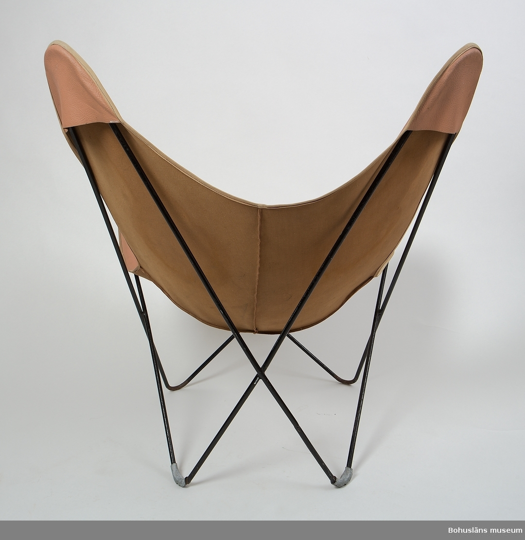 """""""Läderlapp"""", svart järnram, grå plastfötter, sittduk av brun galon (läderimitation) med ljus kant av textil. Galonen sydd av fyra stycken. Använd av grannens dotter, född på 1950-talet i hennes rum på 1950-talet. Grannen Margit Rosenberg, gift med rektorn vid Agnebergskolan. Se även UM016926 - UM016931."""