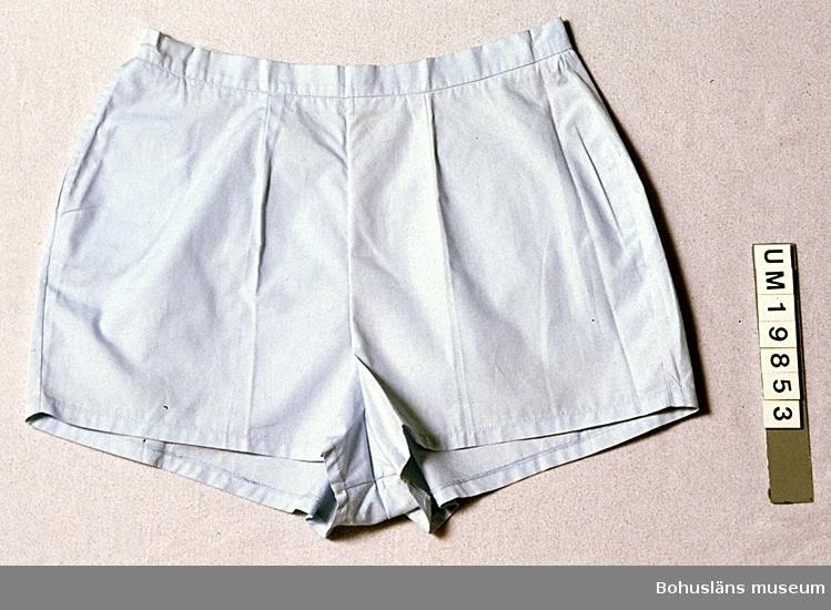 571 Användningstid 1940-TAL? 594 Landskap BOHUSLÄN 503 Kön KVINNA  Ljusblå shorts med ca 5 cm korta ben. Blixtlås mitt bak. Linning som knäpps bak med en vit plastknapp. Sidficka med öppning i höger sidsöm.  Har pressveck. Använda ihop med solliv se UM 19852.  Gulnade upptill. Smutsiga på insidan upptill. Omkatalogiserat 1997-10-02 VBT