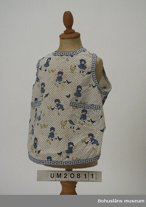 503 Kön KVINNA  Båtformat förkläde med tryckt dekor av flickor och hönor. Två fickor, bård. Elsa Memsen f 1895 moster till givaren.  Personuppgifter se UM 20803.
