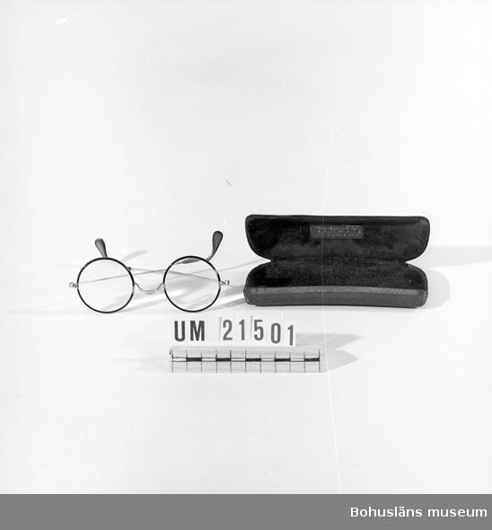 """594 Landskap BOHUSLÄN  Glasögonnen består av två runda glas i skalmar av gulmetall med brun bakelit runt glasen och i skalmarnas ändar. Fodralet klätt med brun plast. Fodralet är klätt inuti med brunt sammet. På insidan locket är ett metallmärke: """"Boström Ur-Optik Tel: 119 Uddevalla"""". Bottens utsida är märkt: """"Brio""""  UMFF 27:5"""