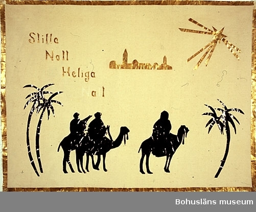 """594 Landskap BOHUSLÄN  Väggbonaden föreställer de tre vise männen på var sin kamel. Med följande text: """"Stilla natt heliga natt"""". N samt t saknas i texten: """"Heliga natt"""". Kameler, män och palmer av svart glättat papper, övriga figurer och omramning av guldpapper.  UMFF 128:1"""