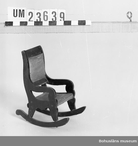 Föremålet visas i basutställningen Uddevalla genom tiderna, Bohusläns museum, Uddevalla.  Gungstol av empiretyp. Ryggstöd och sits klädd med blå bomullssatin?. Furuträet mörkbetsat för att likna mahogny.