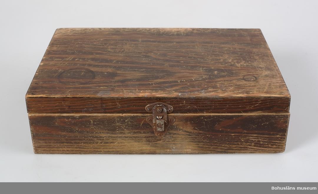 Trälåda med pailjotter för värmepermanent. Föremål från Brorssons Damfrisering i Kungshamn, se UM023941.