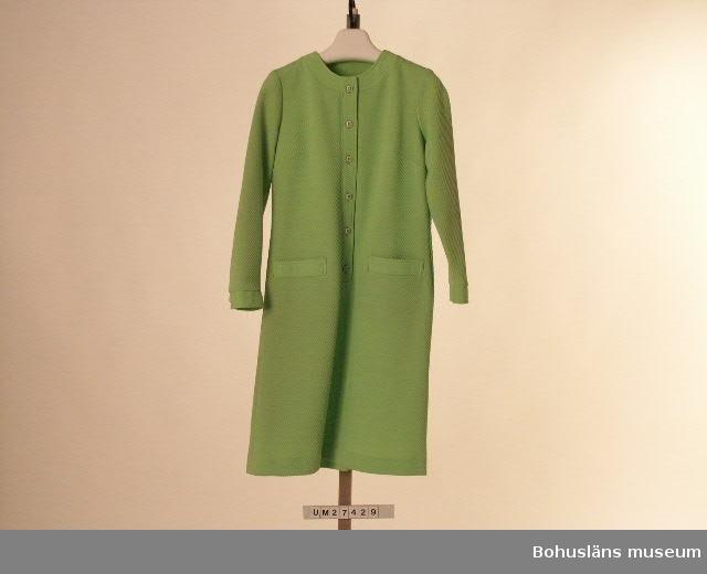 """Föremålet visas i basutställningen Uddevalla genom tiderna, Bohusläns museum, Uddevalla.  Ärtgrön klänning med lång ärm av kraftigare tyg vävt i reliefrandig effekt. Klänningslivets randning är snedställd åt ena hållet och detaljdelar - krage med knappslå, ficklock och manschetter - är snedställda åt andra hållet för dekorativ effekt. Rak, enkel, något utsvängd modell.  Halsringning och 48 cm lång öppning fram med ståkrage och knappslå i ett och samma stycke med sex fyrkantiga, gröna plastknappar samt knapphål. Likadana knappar på ärmmanschetterna. Infällda fickor med ficklocksmarkeringar. Bystveck och armbågsveck. Ofodrad. Etiketter i knappslån med med texten: """" 'Magnalene' 100% CRIMPED POLYESTER 40""""  Saknar pappersetikett. Obegagnad vid förvärvet.  För ytterligare uppgifter om förvärvet och övrigt material rörande Magnas produktion i museets samlingar, bl.a.  dokumentation 1998, se UM270416"""