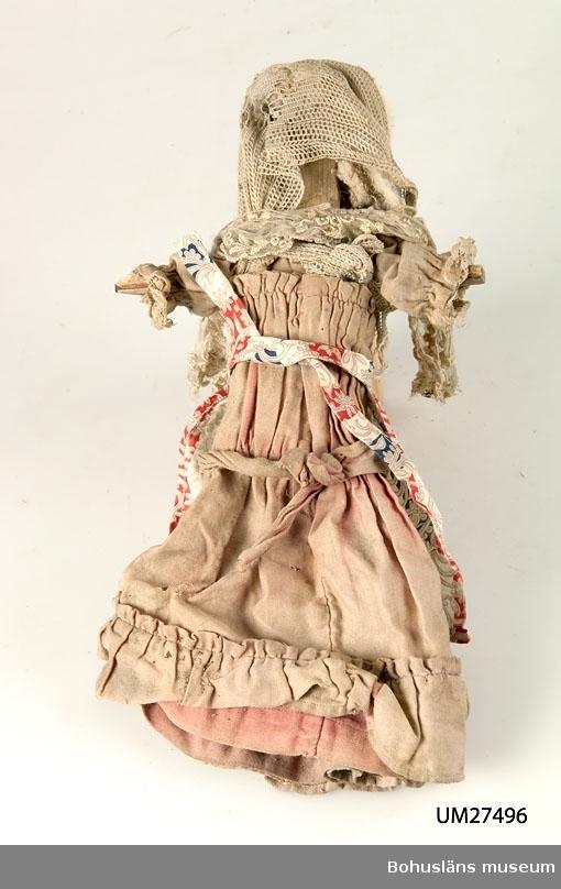 Hemmagjord trädocka från tidigt 1900-tal. Dockkroppen är grovt utskuren ur ett stycke furu och har ansikte med antydan till mun, näsa och ögon, påspikade armar som står rakt ut utan händer och raka ben utan fötter. Hår i form av bomull. Dockan är klädd i  en mycket blekt rosa klänning av sekelskiftessnitt med volang och garnering och med huvud- och axelschal av vit spets. Klänningen verkar ha hört till en annan, finare dockkropp.  Enl. givaren kan dockan ha tillhört Ingeborg Hammar i Dragsmark,  f. 1916. Huset där dockan är funnen är byggt 1916, Klostergård 3, Dragsmark.  Dockan är funnen i huset sommaren 2000 under en golvbräda på  vinden.