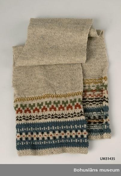 Stickad halsduk i ullgarn. Mönster i de två ändarna. Mosstickad utom i de båda ändarna där mönstret Blå randen använts. Obetydliga hål. Tvättad.