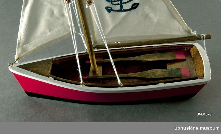 Segelbåt för prydnad.  Mahognyplywood eller liknande, röd bordläggning med vit rand, svart bottenmålning och invändigt klarlackad. Amerikansk dory-typ, plattbottnad med storsegel och fock och ett par åror, tofter och förlig kapp.  I seglet ett ankare tryckt med blå färg och ovan texten WELCOME ABOARD. I botten etikett MADE IN CHINA. På butikens följesedel benämnd: Segelbåt röd, liten. Inköpt i Lysekil  till föremålssamlingarna i samband med utställningen Fri och ledig!? sommaren 2011.