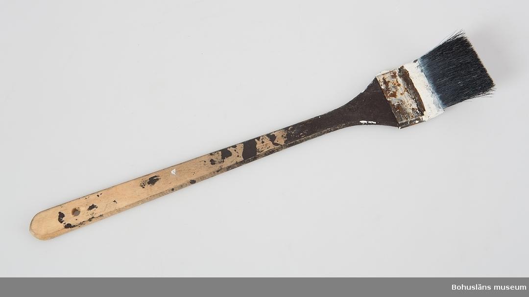 Vinklad flat målarpensel med skaft av björk och naturborst. Märkt NIDRON Rester av vit och svart färg.