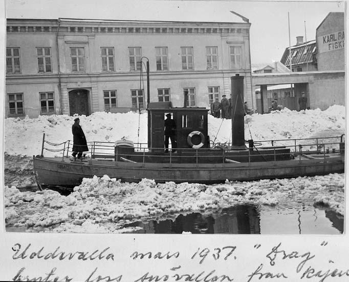 """Text på kortet: """"Uddevalla mars 1937. """"Drag"""" bryter loss snövallar från kajen. Lotsen Ödwall står i fören""""."""