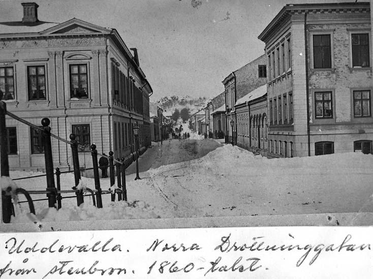 """Text på kortet: """"Uddevalla. Norra Drottninggatan från stenbron. 1860-talet""""."""