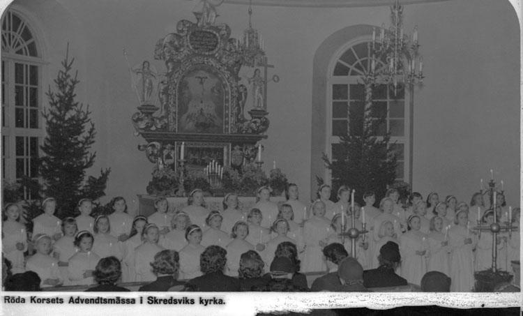 """Enligt AB Flygtrafik Bengtsfors: """"Skredsvik"""". Enligt text på fotot: """"Röda Korsets Adventsmässa i Skredsviks kyrka""""."""