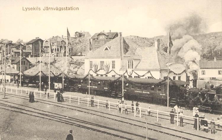 """Tryckt text på kortet: """"Lysekil. Järnvägsstation."""" """"Förlag: A. Hörnfelts Cigarraffär."""""""