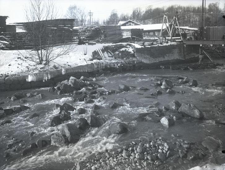 """1935. 28. Bron sönder vid Munkedals fabrik."" ""Munkedalsälven. Emballagevirke i buntar, liten såg, gavelspetsen på arbetarbostaden i bakgrunden."""